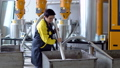 Production plant worker Works with loader Hose vacuum sucking white virgin plastic granules from 56584389