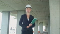 Female construction manager with blueprint on building site presenting the project looking at camera 56604762