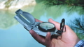 Close up on compass instrument in gloved hand . Mountain hiking trails. Winter mountain trip concept 56640571