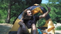 A man is sitting in a tent in a green forest near the lake. Makes a video call on a smartphone to 56640589