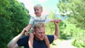 Happy young father holds his son piggyback ride on his shoulders and looking up. Little boy is 56640603