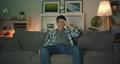 Portrait of attractive Asian guy watching TV having fun laughing in dark room 56726208