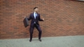 Attractive man with a beard and briefcase dancing in the city street. Against the background of a 56746754