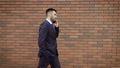 Businessman dressed in shirt talking smartphone while walks on the background of a modern brick wall 56747171