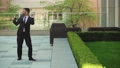 Happy businessman listening to music in headphones on smartphone, walking outside the office and 56747830