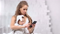 Busy young mother chatting using smartphone holding little baby by hand at white room interior 56816138