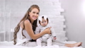 Adorable smiling young mother sitting on bed posing with newborn child looking at camera 56816161
