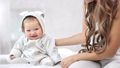 Smiling baby wearing cute overall sitting on bed having positive emotion looking at camera 56816594