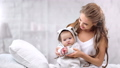 Beautiful smiling mother playing with cute baby clapping hand feeling love surrounded by light 56816604