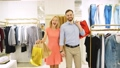 young happy couple shopping together clothes at fashion shop. Slow motion. 56881373