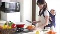 抱っこ紐で料理をする女性 キッチン 56936801