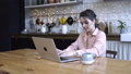 Concentrated young woman sitting in the kitchen at wooden table and typing on her personal silver 56959366