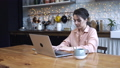 Concentrated young woman sitting in the kitchen at wooden table and typing on her personal silver 56959367