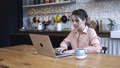 Concentrated young woman sitting in the kitchen at wooden table and typing on her personal silver 56959369