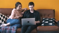 Wonderful young couple sitting on the couch at home and watching to laptop screen. Stock footage 56959371