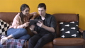Close-up view of happy young couple sitting on the couch at home and watching to tablet screen 56959385