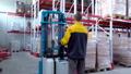warehouse worker driver in uniform loading cardboard boxes by forklift stacker loader 56973956