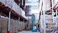 warehouse worker driver in uniform loading cardboard boxes by forklift stacker loader 56974494