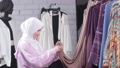 Concept of shopping in Muslim countries. A young Muslim woman choosing clothes at the store 56994808