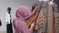 Concept of shopping in Muslim countries. A young Muslim woman choosing clothes at the store 56994813