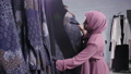 Concept of shopping in Muslim countries. A young Muslim woman choosing clothes at the store 56994814