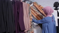Concept of shopping in Muslim countries. A young Muslim woman choosing clothes at the store 56994815