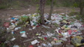 Large illegal dump on a forest trail. A bunch of plastic, bags, bottles and other waste pollutes the 57024972