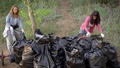 Female volunteers finish cleaning in nature. The girls put a large garbage dump in plastic bags 57024999