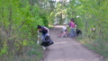 A group of women and children collect garbage in the forest. Volunteers collect plastic and other 57025103
