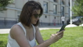 Portrait of young pretty woman in white T-shirt texting on smartphone on office building background 57059988