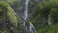 Water river falling from inside a waterfall in slow motion. Waterfall in the Caucasus mountains. 57060761