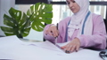 Small business and hobby concept. Muslim woman fashion designer pinning paper pattern at the table 57065365