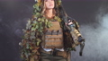 Camouflaged woman sniper in ghillie suit posing with rifle in foggy night 57111410