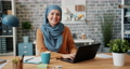Portrait of Muslim girl in hijab smiling looking at camera in office at desk 57143715