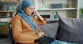 Ambitious Muslim girl working with laptop and talking on mobile phone at home 57146131