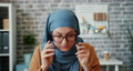 Muslim girl in hijab putting on glasses and looking at camera in office 57146142