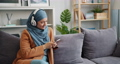 Cheerful Muslim girl in hijab using smartphone listening to music in apartment 57146154