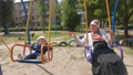Grandmother with a grandson on a swing 57151154