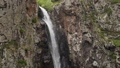 Slow motion shot of waterfall flowing down the rock. Camera moving down 57201195