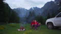 Couple chatting by bonfire in a camping in a dark mountain valley. White car 57201200
