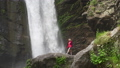 Hiking woman in red jacket walking near big waterfall 57293817