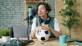 Happy teenager talking in microphone in recording studio holding football 57458367