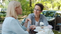 Attractive adult women speaking in outdoor cafe gesturing at table with drinks 57459749