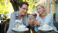 Excited women using smartphone laughing in open air cafe in city street 57459752