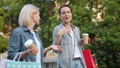 Happy women chatting walking in park with bright shopping bags and coffee 57459766