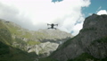 Drone with Rotating Propellers Hanging in the Air on a Background of Lake and Mountains. Drone with 57519379