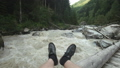 A man sits on a wooden bridge, legs dangling down. A fast mountain river flows. Mountain travel. 57519380