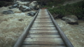 A wooden bridge over a fast mountain river 57519381