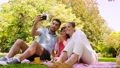 family having picnic and taking selfie at park 57625087