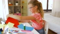 girl cutting color paper with scissors at home 57625091